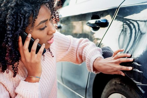 woman on cell phone examining scratches on car