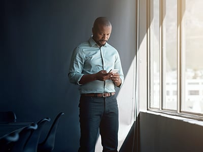 Shot of a mature businessman using a mobile phone in a modern office