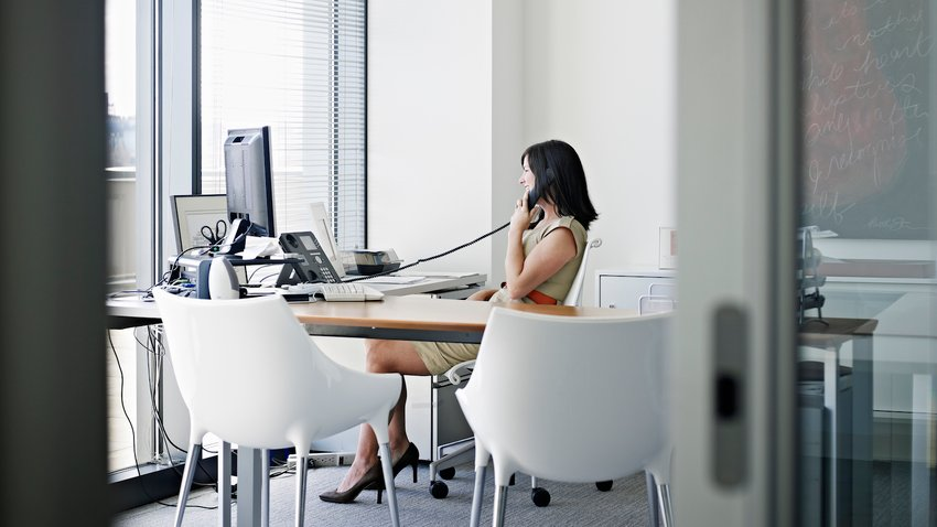 Businesswoman sitting at desk in office talking on phone smiling