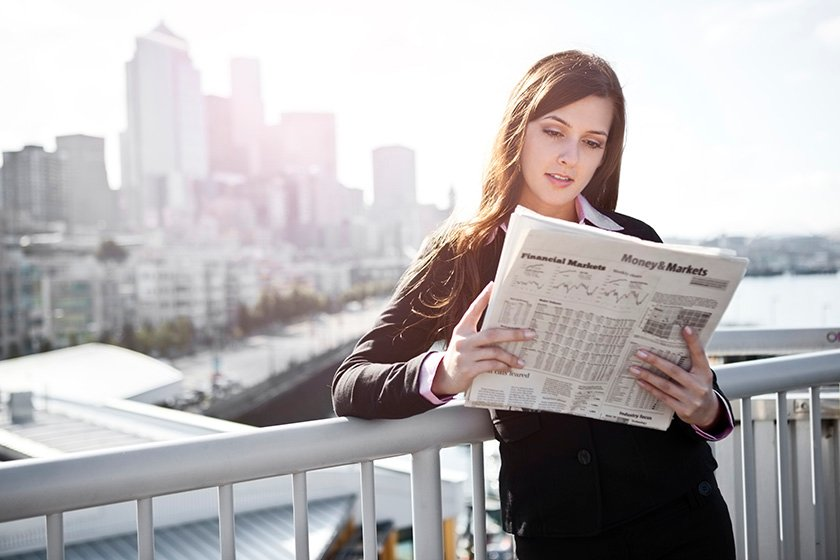 Woman leaning on fence reading newspaper