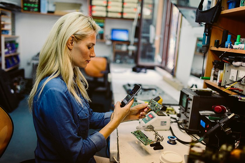 Woman looking at phone while fixing equipment